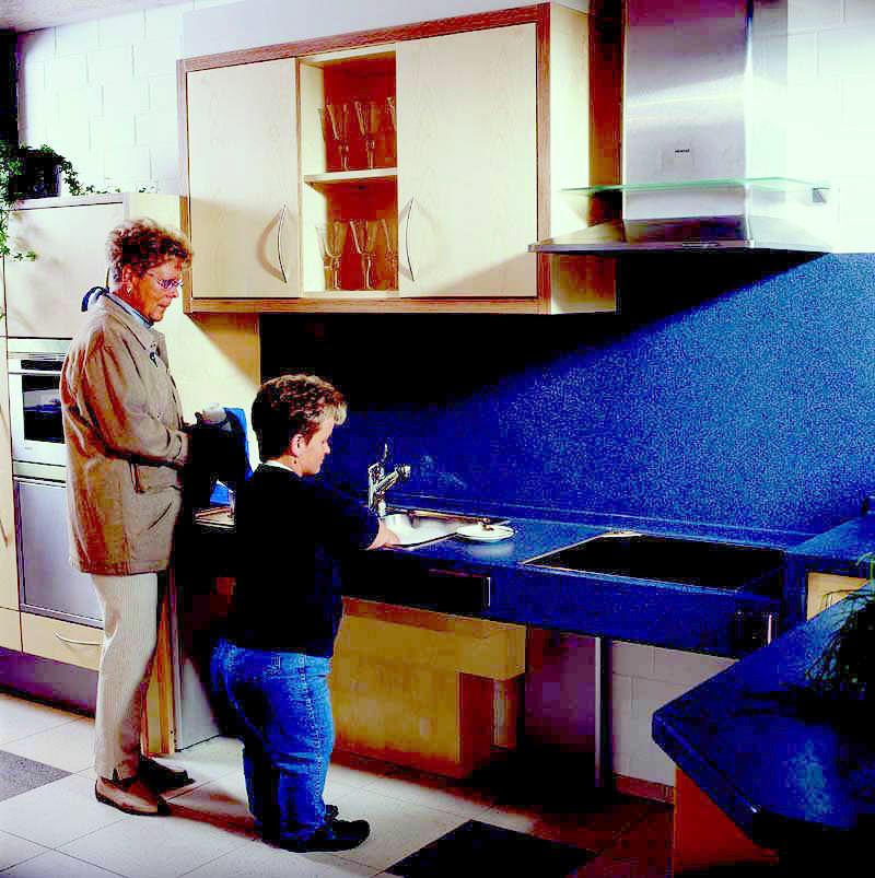 Elektrisch verstellbare Oberschränke und Arbeitsplatten sowie Auszüge sind für Groß und Klein leichter erreichbar.